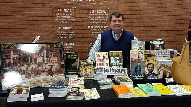Local author Jon Musgrave of Marion displays some of the many local history books he carries at Heritage Fest Sunday.