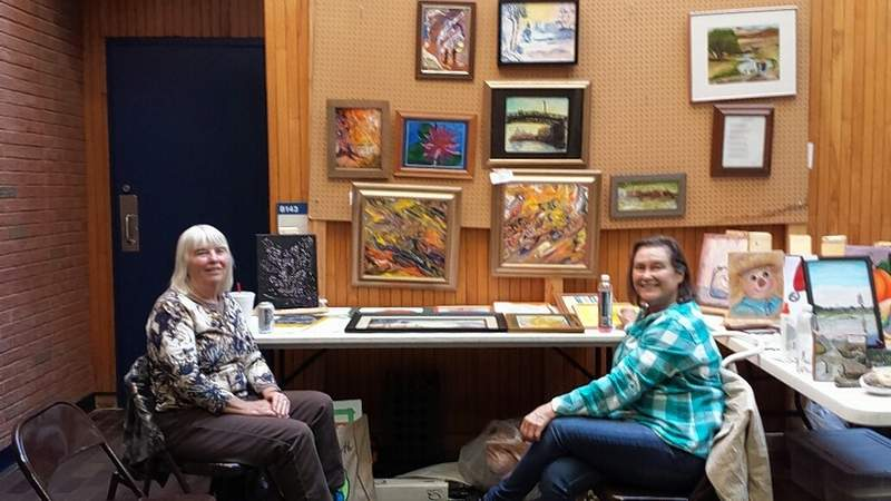 Eldorado artist Janet Bixler, left, and Diane Berry take a break from a conversation at Heritage Fest for a photo.