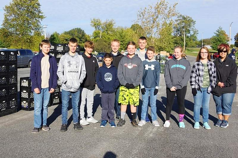 From left, St. Mary's Catholic School students who helped at the October distribution are Luke Schuwerk, Gage Hopkins, Kolton Jany, Jonathan Hayer, Ethen Colvis, Nate Maes, Garret Hopkins, Jack Heffernan, Grace Welborn and Elseah Congiardo. Teacher Pam Fogerson is at right.