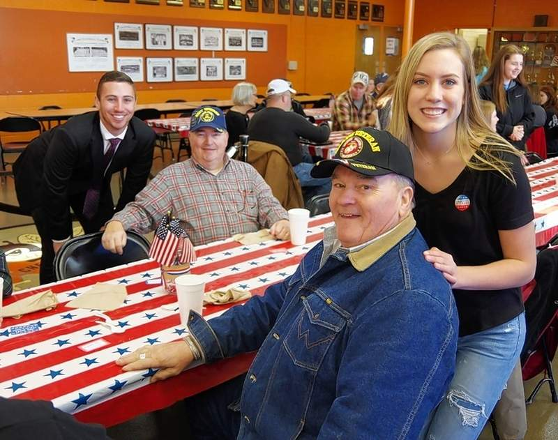 History teacher Jake Cowan (back) greets veterans Bill Ebers (sitting behind) and Steve Herrell (sitting front) as Herrell's niece Kennedy Herrell (standing front) socializes with Uncle Steve Herrell. Cowan coordinated the breakfast while Kennedy Herrell served breakfast and greeted veterans
