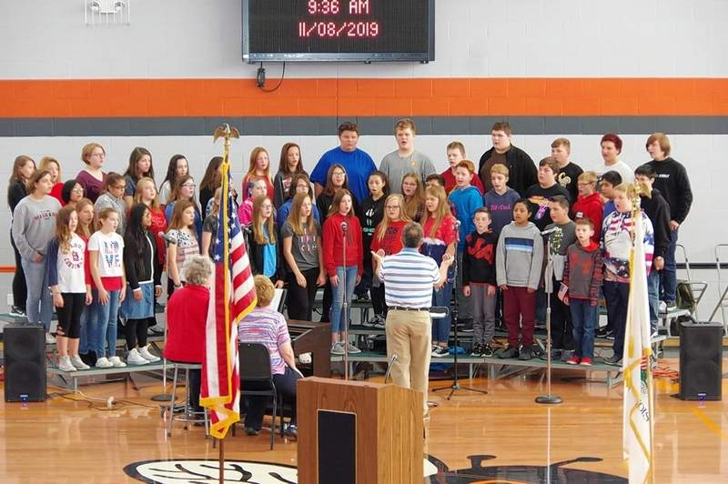 """Steve Colonel leads the junior high chorus in """"God Bless the USA."""""""