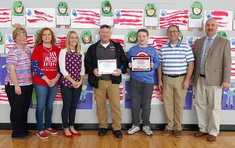 The team that put the Veterans Day Assembly together, from left: Sue Colonel, Mary Bohnert, Casey Peters, Chief Bobby Helmers, David August, the 6th grade poem winner, Steve Colonel and Principal Bill Grafton.