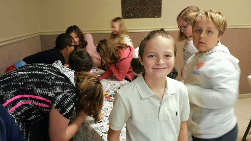 East Side fifth grader James Cranmore stands at an activity table Monday at the Thanksgiving dinner his class and teacher, Benjie Willsey, hosted for members of the local community. Cranmore invited the Harrisburg Register/Eldorado Journal.