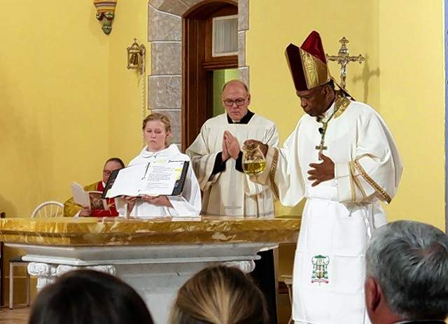 Bishop Edward Braxton pours holy oil on the new altar during the rededication service at St.Mary's in Chester.