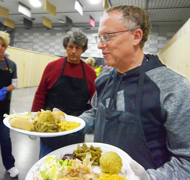 Jeff Goffinet delivers two Thanksgiving dinners to diners Thursday. Goffinet was among the small army of volunteers who helped out at the communitywide Thanksgiving dinner.