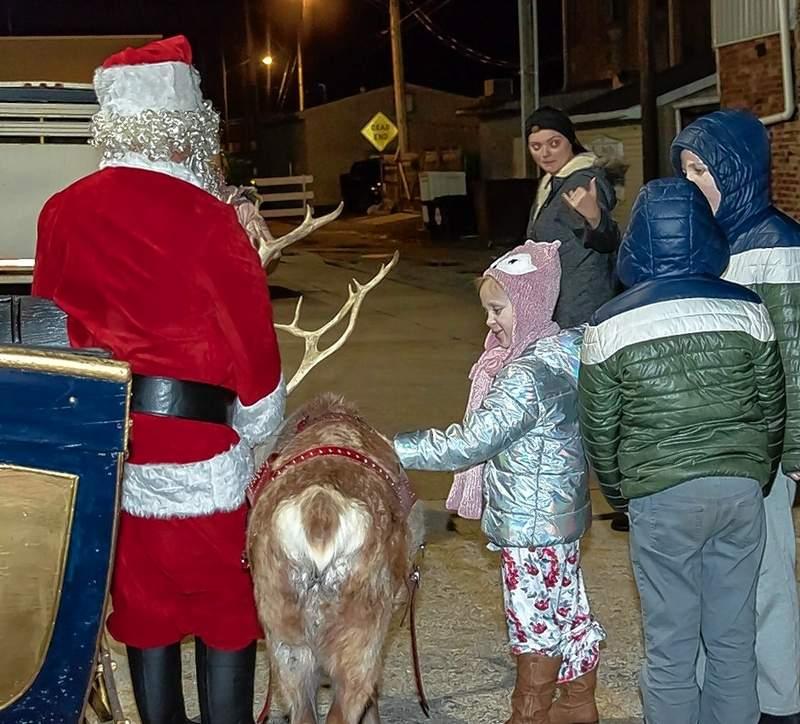 Santa's reindeer gets a little petting from a fan.