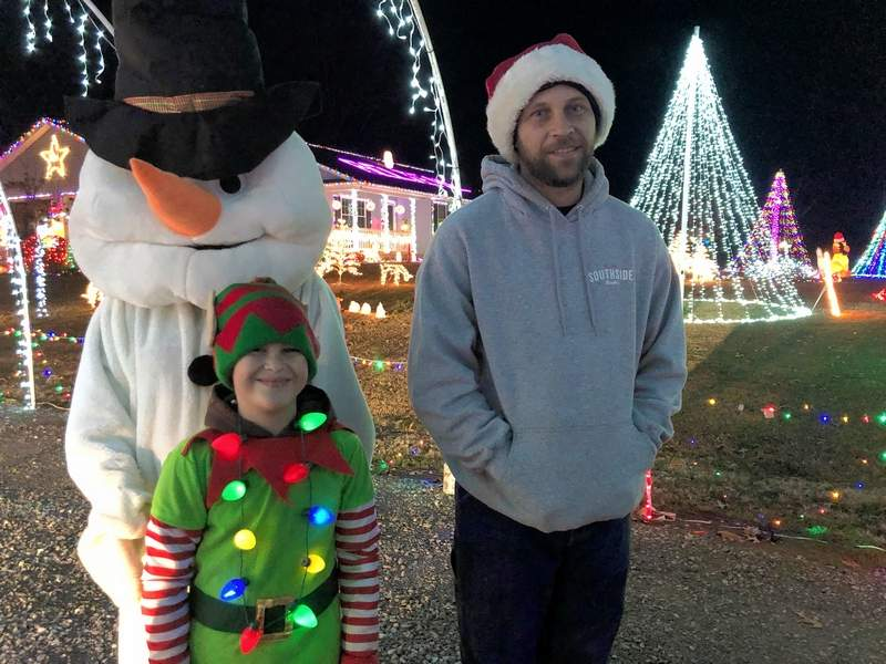 The Yost Family, grandmother, Debbie, as a snowman, 8-year-old Ethan, the elf, and his dad Cody, have an incredible light display in rural Marion that attracts hundreds of visitors each week during the holiday season.