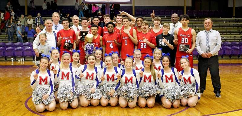 Members of the Massac County basketball team, including coaches and cheerleaders, pose with the 55th Annual Eldorado Holiday Tournament championship after taking down Fairfield 57-51 in Saturday night's title game.