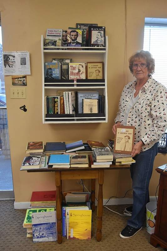 TRAVIS DENEAL PHOTO Josie Brooks, owner of the Book Emporium in Harrisburg, stands next to her collection of local history books for sale.