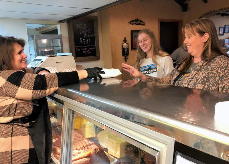 P&R employee Tammy Sanders, left, greets regular customers Sydney Allen and her mom, Stephanie, at right.