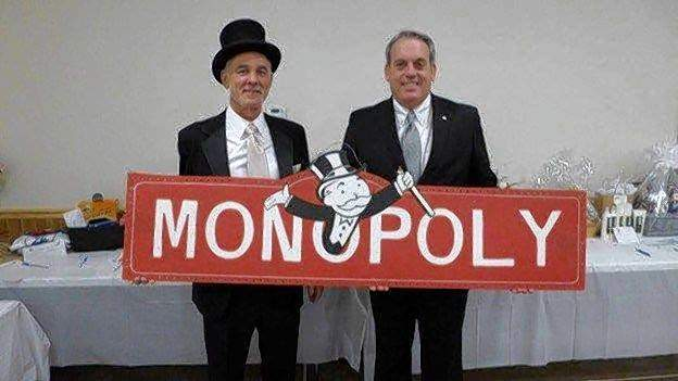"Fowler Bonan Foundation Executive Director Kerry Camp, left, and state Sen. Dale Fowler hold a Monopoly sign in this photo promoting last year's ""Roger Craig Memorial Monopoly Tournament."" Camp and Fowler will reprise their roles in this year's tournament."