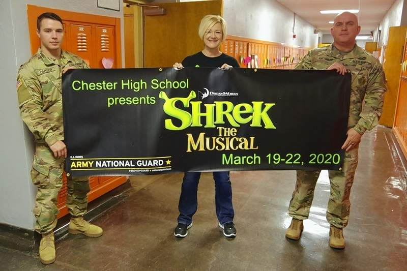 "Theater director Brenda Coop shows off the banner advertising the upcoming production of ""Shrek the Musical,"" alongside Army National Guard Recruiters CPL Anthony Carter and SFC Dane Patterson. The Army National Guard marketing office in Springfield made the banner."