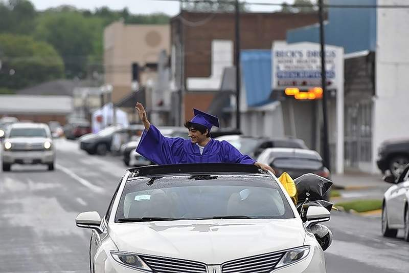 An EHS grad waves at the crowd during the graduates parade.