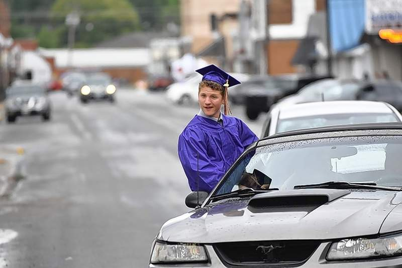 An EHS Class of 2020 grad hangs out of the window of a car during the graduates parade.