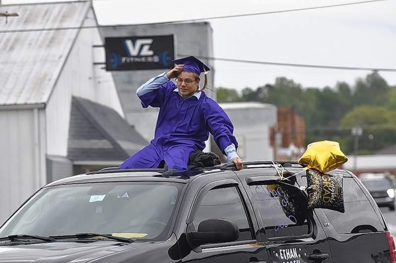 EHS Class of 2020 grad Ethan Goren hangs on as the car he's in turns a corner in the Eldorado graduates parade.