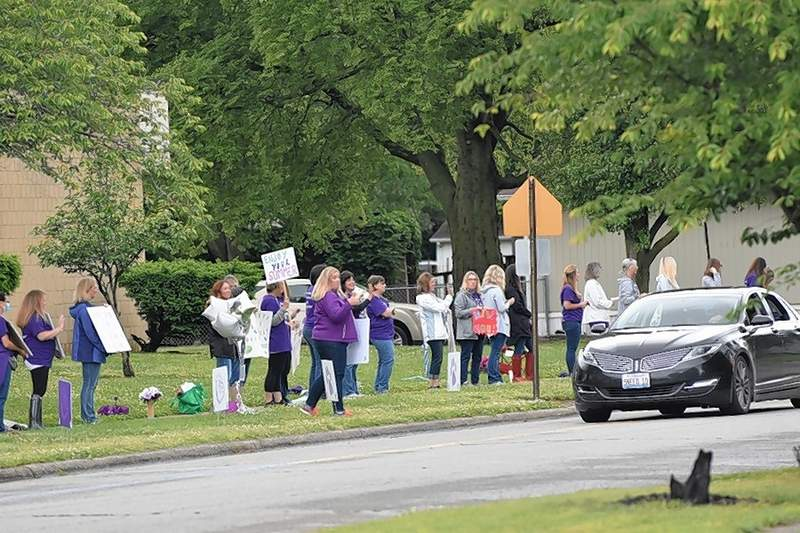 Teachers and staff at West Side hold signs and cheer as students are driven by on Tuesday.
