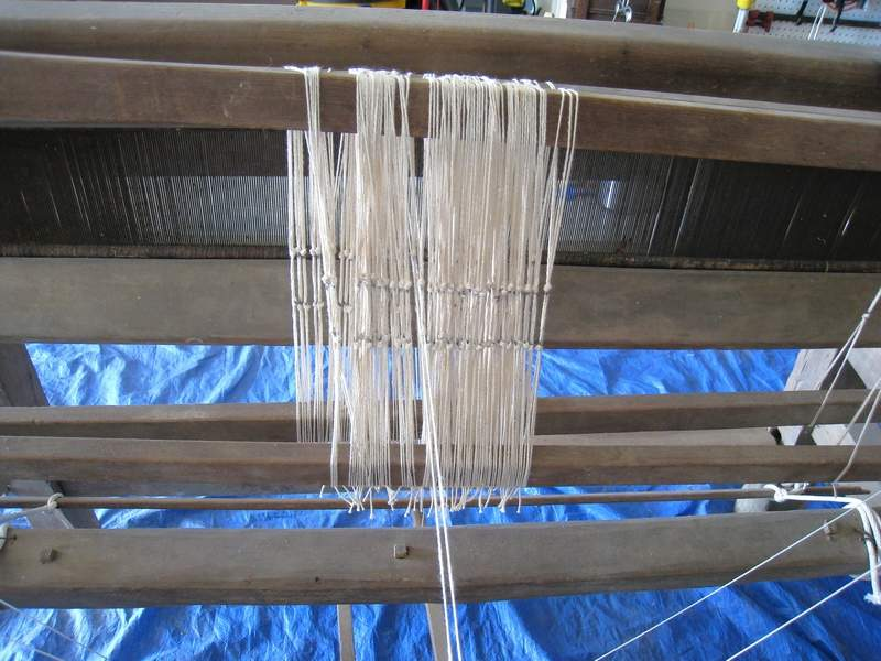 Threads in the beginning stage of weaving on the barn loom.