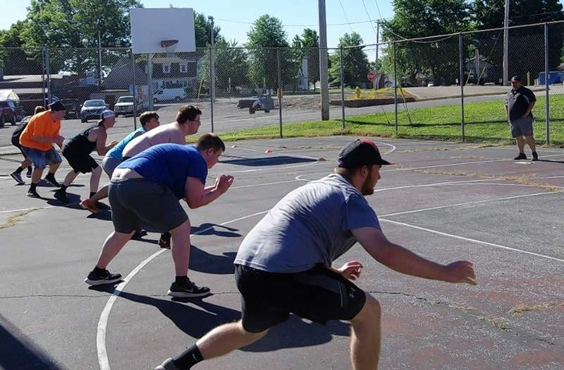 CHS Head Football Coach Billy Belton guides the varsity Yellow Jacket players work on conditioning June 24 on the CHS basketball courts.