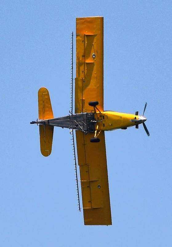 A crop-duster passes overhead in rural Saline County.