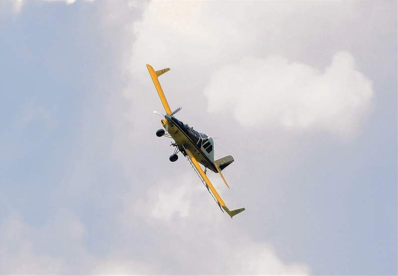 A crop-duster flies over a field in rural Saline County.
