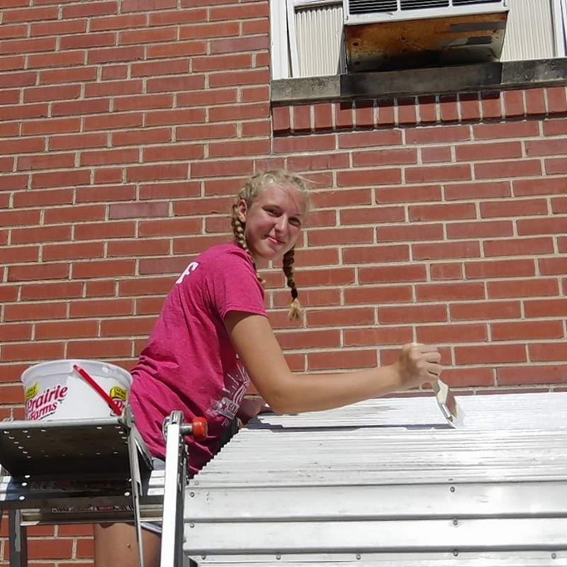 Katie Schumer paints the awning leading into the First United Methodist Church Fellowship Hall.