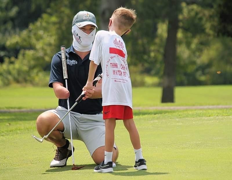 NubAbility Coach Sam Monarch helps Ryan Eilers with his golf club grip at the Aug. 15 regional golf camp.