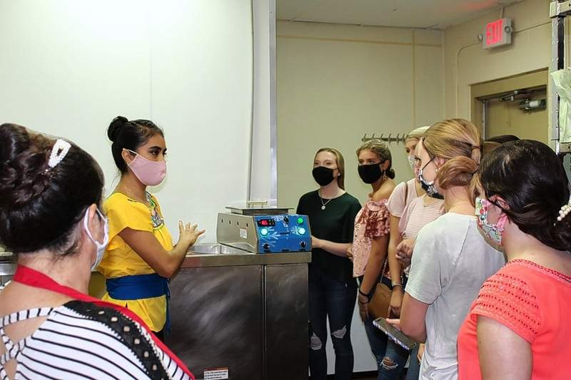 "La Galeria owner Laura Chairez, back left, explains how she operates various components of her business to those attending Victoria Shore's ""Lead Like a Girl"" summit in Marion on Sunday."