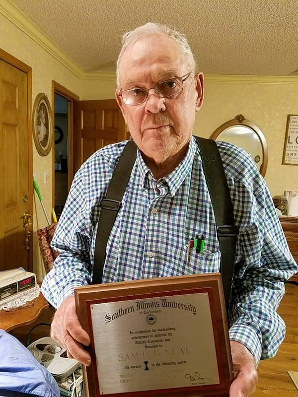 Sam DeNeal, with his recognition from SIUC for outstanding achievement in athletics in track (1954, 1955) and cross country (1956, 1957). The plaque was presented to him by former SIUC Athletic Director Gale Sayers.