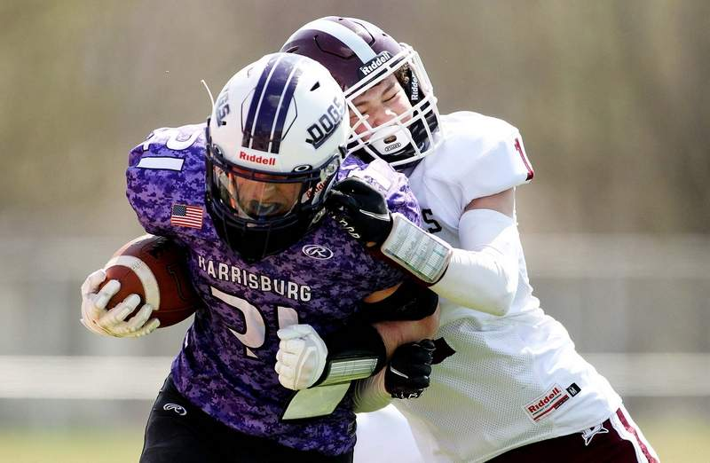 Harrisburg sophomore Ross Rider works upfield while being tackled by Benton's Reid Baumgarte in the second half Saturday at Taylor Field.