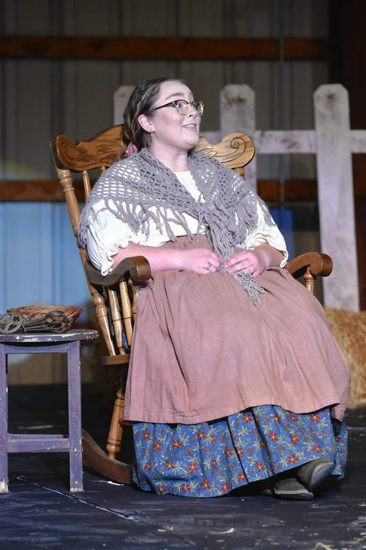 """Aunt Eller, played by Ravyn Gauch, rests in a rocking chair in a rehearsal for """"Oklahoma!"""""""