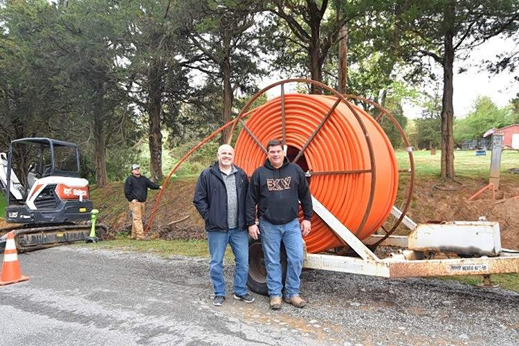Shawnee Communications Sales & Marketing Manager Andy Henderson, left, stands in front of a large spool of orange duct that will contain new fiber optic cable with BKW Services Inc. President Kevin Wenthe.