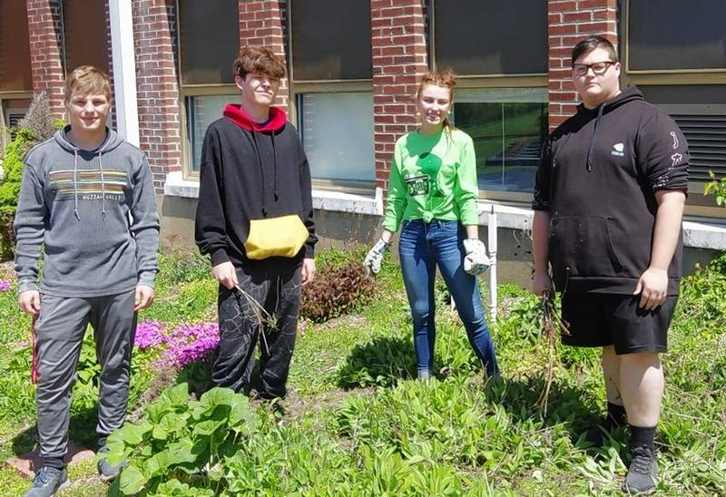 Caleb Parker, Hunter Riedel, Amelia Shemonic and Alex Martin Sr. clean brush and debris from the flower bed at Chester High School.