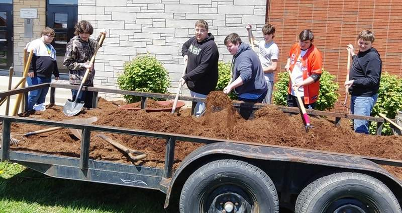 Chester High School students load fresh mulch donated by Mary Ann and Robert Heberlie into wheelbarrels.