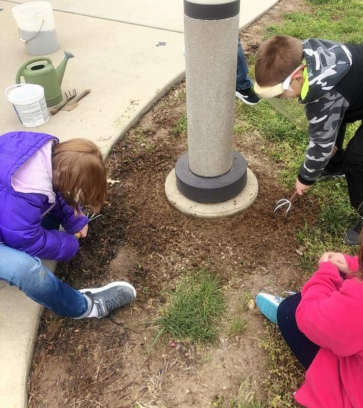 """Another Earth Day project was underway at Chester Grade School, where students in Lynne Gonzalez's class planted flower seeds near the school entrance and picked up trash on the grounds. """"I just helped the Earth!"""" one kindergartner told Gonzalez on their way back into the classroom."""