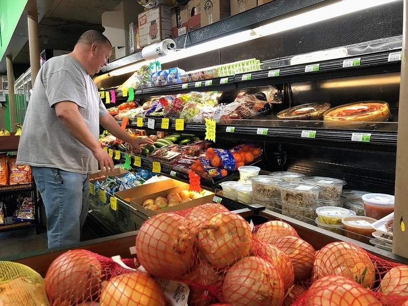 New owner Dave Reynolds checks the produce stock at Small's Grocery.