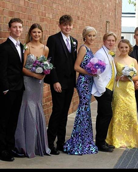 From left, Mason Gilliam of Carrier Mills, Missy Chamberlain of Harrisburg, Eli Grathler of Carrier Mills, Hannah Proctor of Harrisburg, Brandon Banks of Harrisburg and Jersey Willis of Harrisburg pose for a prom photo prior to a wreck the night of Harrisburg High School's prom on May 1.