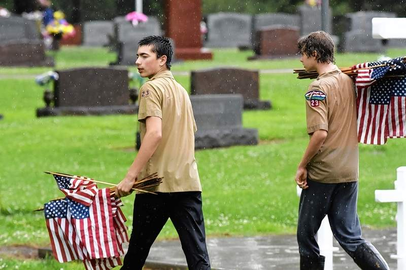 Harrisburg Boy Scouts Justin Horn, left, and Justin Haney weren't slowed down by a sudden heavy downpour Wednesday, continuing to place flags at veterans' grave markers.