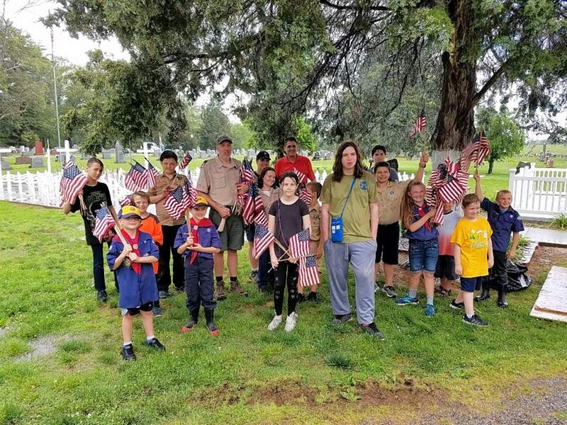 Cub Scouts and members of Scouts BSA Troops 7023B and 7023G from Harrisburg join Harrisburg Mayor John McPeek while placing flags at veterans' grave markers for Memorial Day Wednesday evening.