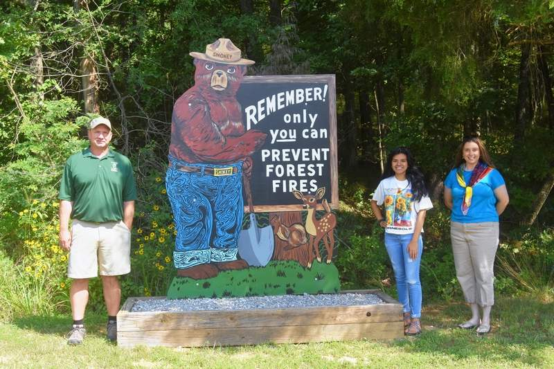 Saline County Fish and Wildlife Site Superintendent Eric McClusky, left, stands next to the restored Smokey Bear sign at Glen O. Jones Lake, along with SIC student artist Marisol Walle, second from right, and former SIC art instructor Sara DeNeal. Art students Trenton Johnson and Mackenzie Gidcumb also worked on the sign project.
