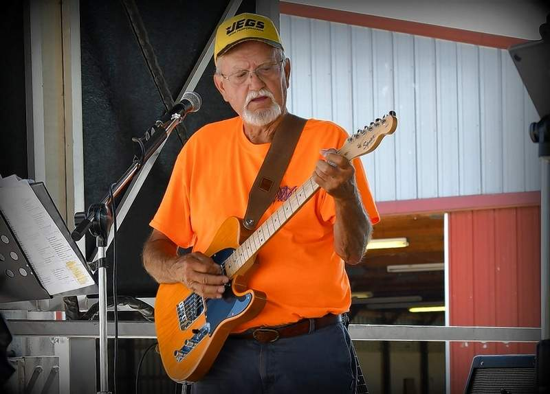 Dennis Wilson, who plays music with his daughter, Jodi McKnight, in the band Last Call, entertains on the car show stage. When he's not making music, Dennis is a professional auctioneer.