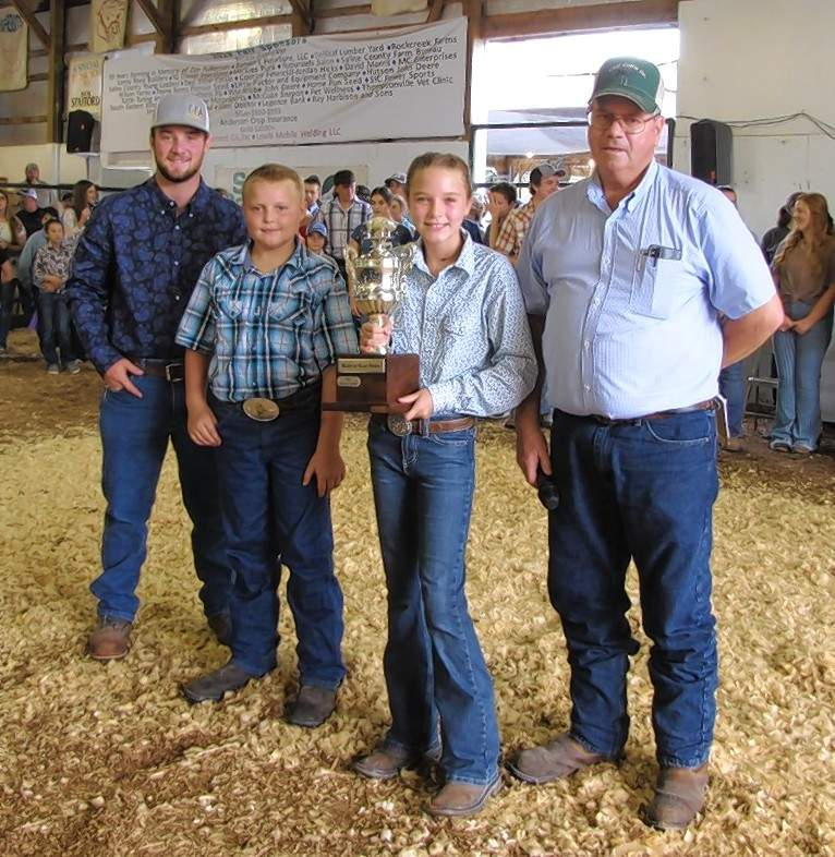 The top five Daily Rate of Gain market swine owners Davis Evans and Caleb Boulds, and 2021 Swine Rate of Gain trophy winner Avery Rash, are pictured with Dan Evans. The Swine Superintendent was Sam Glenn with help from Sara Oxford.