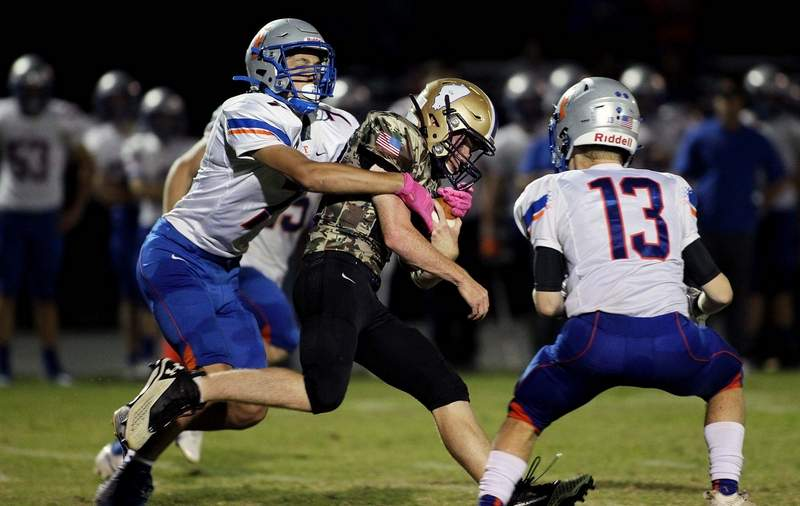 Eldorado's Brock Cantrell tries to shed a couple of Flora defenders in the second half Friday night at Boz Adams Field.