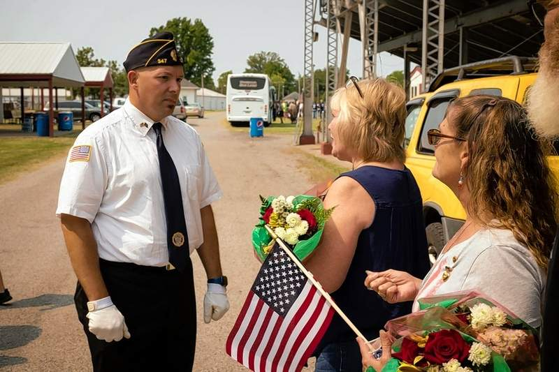 Army Veteran Tom Harness hands shotgun bullets to the parents of two local fallen soldiers from the 21 gun salute held during the Williamson County Fairgrounds Memorial.