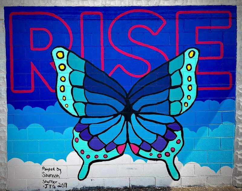 """Before the Marion Mural Project was conceived, Savannah Sheffler began a butterfly mural on the APC Marion Marine building, but moved from Marion before she had a chance to complete it. Marion Cultural and Civic Center Executive Director Josh Benson decided to complete the mural. """"It's the perfect height for anyone of any age or height to pose with the wings,"""" he said. The new mural can be found on the corner of Union and Mechanic Streets."""
