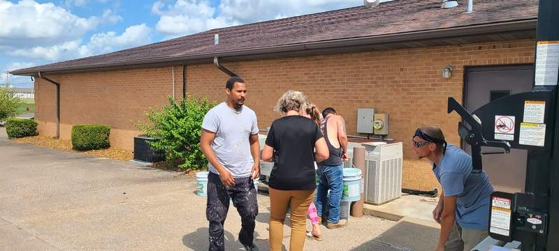 Volunteers work to unload buckets of laundry soap from the recent fundraiser held by the Williamson County Heartland Rotary.