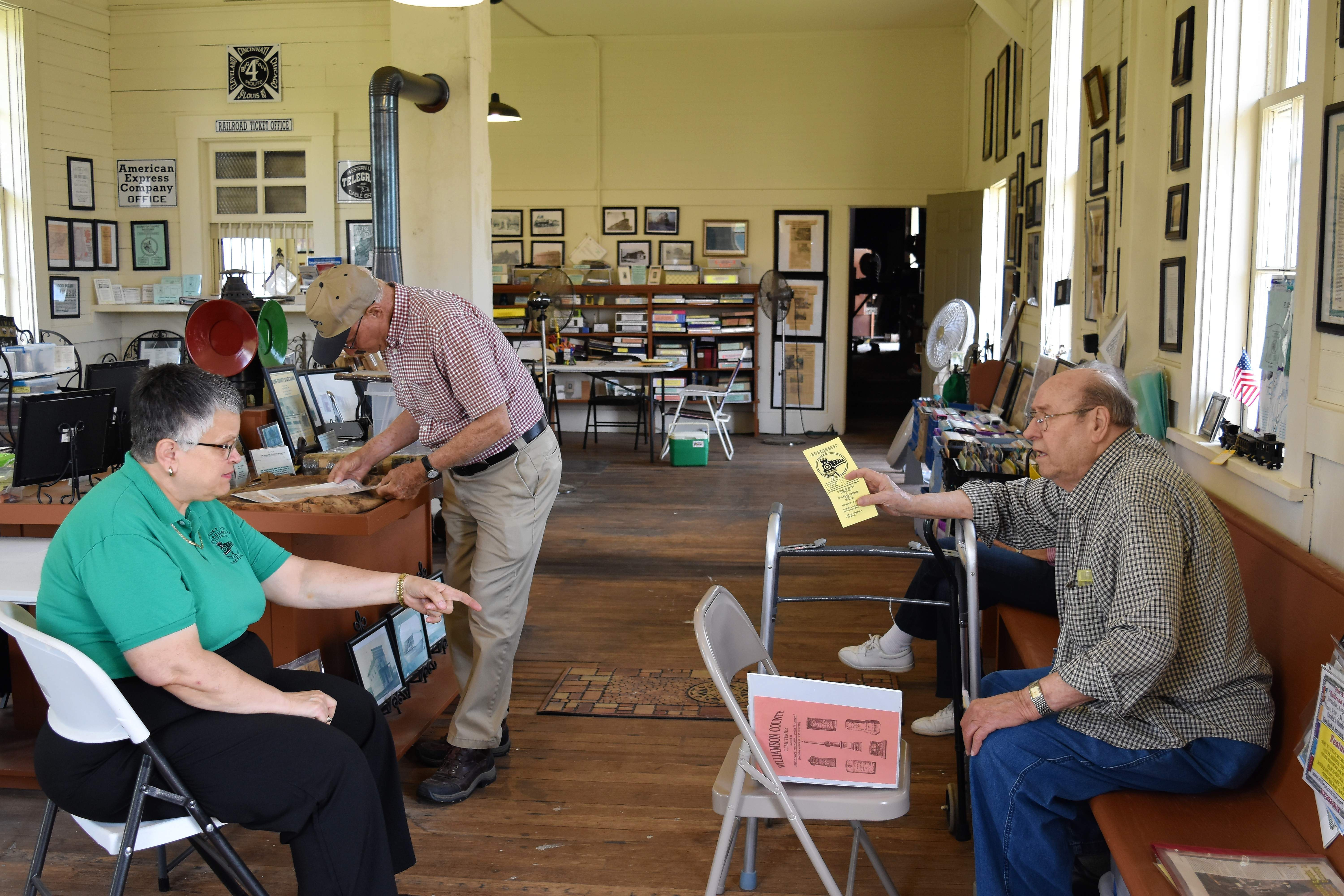 Linda Blackman, left, owner and curator of the Stonefort Railroad Depot Museum, talks with Wendell Hundley of Waterford, Mich., Tuesday afternoon. Kenneth Yandell, who lives near Tunnel Hill with his wife Mary and is a cousin of Hundley's, examines a display.