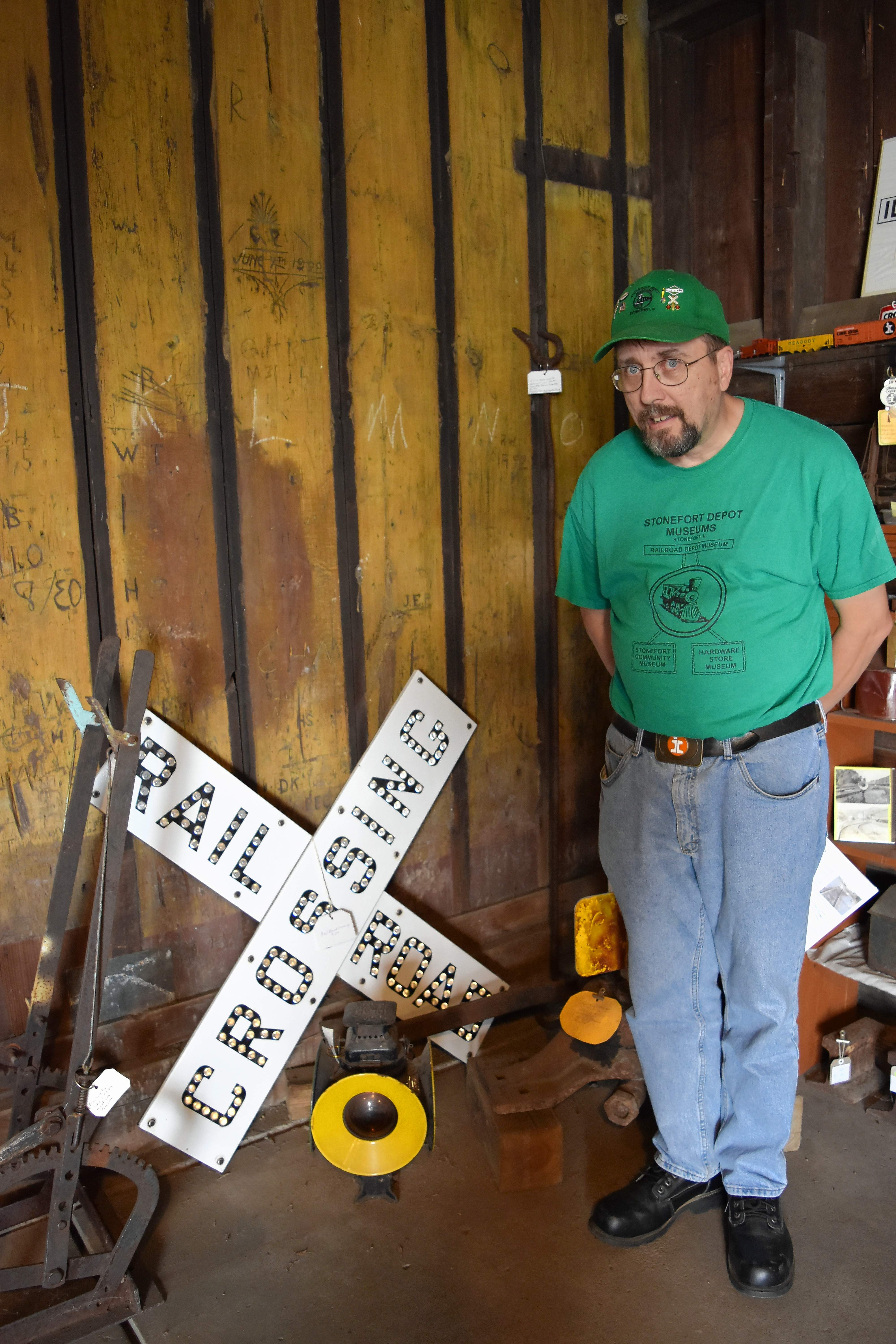 Ralph Maxfield, a volunteer assistant at the depot museum, stands next to a railroad crossing sign he donated. Maxfield has been collecting railroad memorabilia and related items for many years and has been a regular donor to the museum.