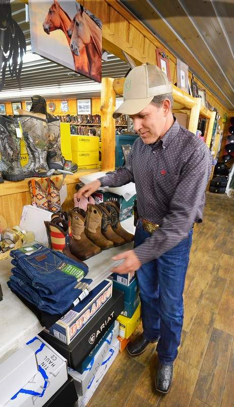 Marion western wear store owner Rick McKinney lays out four pairs of Wrangler jeans and some Durango boots for Mason Ramsey to try on.