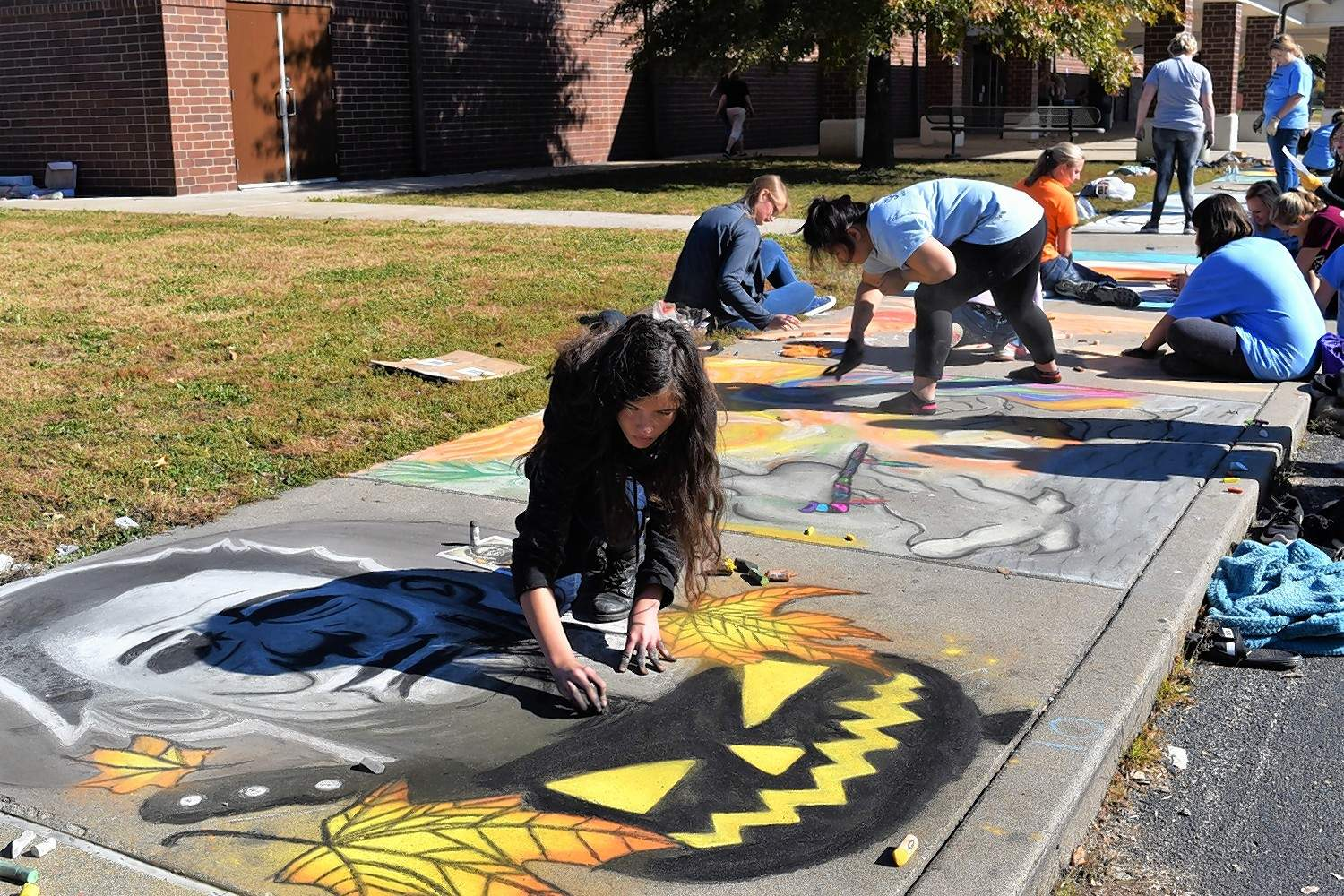 A student artist creates a Halloween-themed image with Michael Myers' mask, a knife and a jack-o'-lantern at Harrisburg High School's chalk contest Monday.