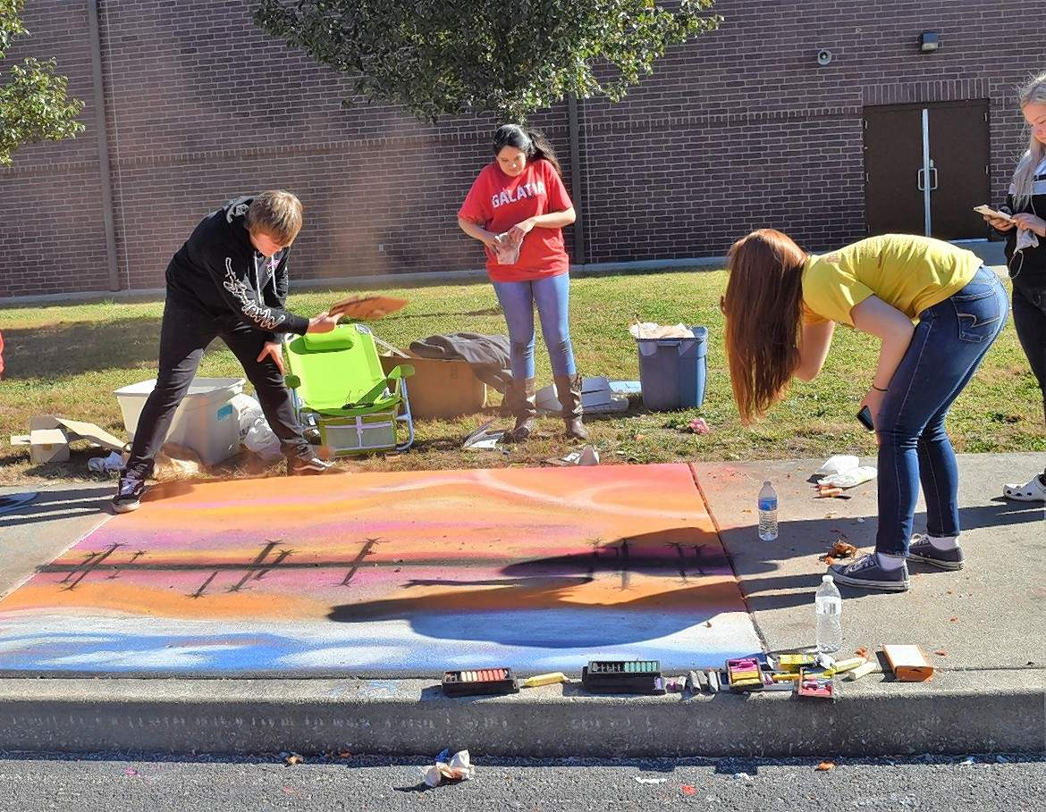 A Galatia chalk contest team whisks excess chalk dust from the team's entry. From left are team members Tristan Mitchell, Briana Rojas, Elliana Field and Maycee Murphy.